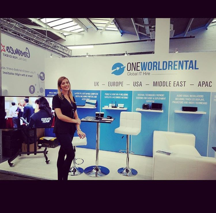 event technology stand at conference with smiling female staff member.