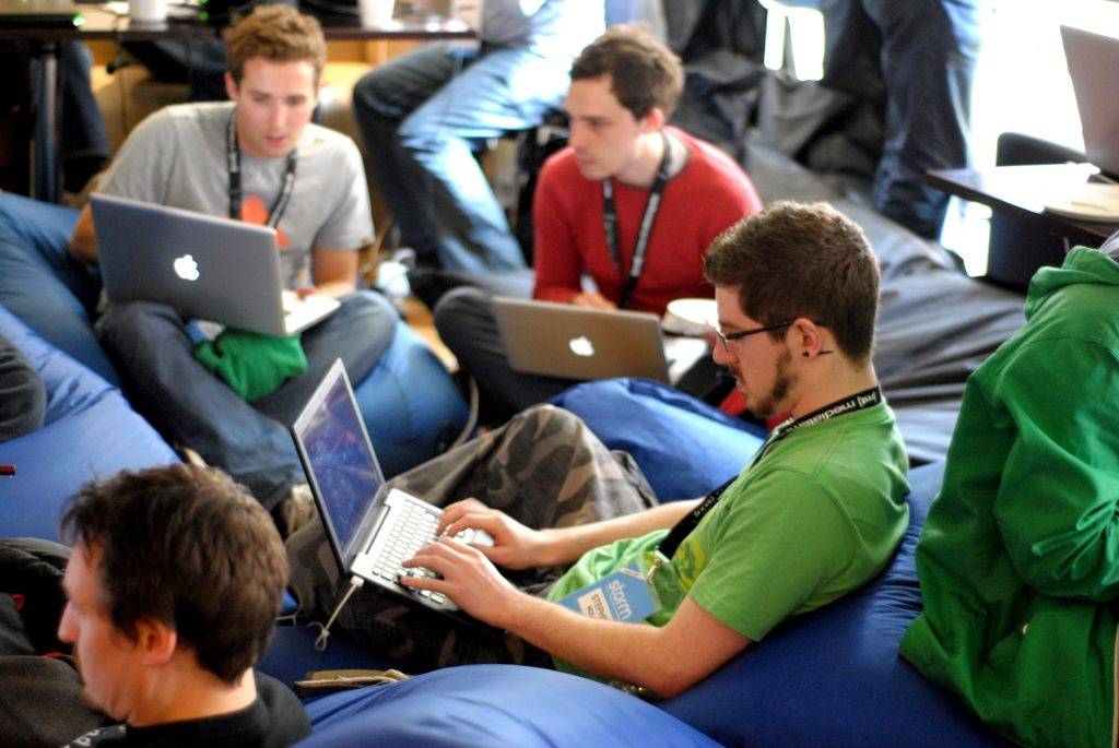team typing on beanbags on their MacBooks